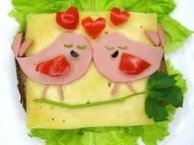 Le sandwich créatif à nourriture avec la saucisse et le fromage a servi sur la laitue Images stock