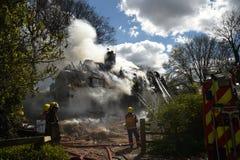 Le sapeur-pompier arrose vers le bas un feu au jet dans un cottage couvert de chaume Photo stock