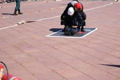 Le sapeur-pompier d'hommes dans le costume et le casque ignifuges enregistre l'homme de travailleur de tractions d'entraves hors  photos stock