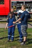Le sapeur-pompier de Berlin montre un groupe de qualifications d'enfants du travail avec la lance à brouillard images libres de droits