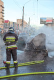 Le sapeur-pompier est près de véhicule brûlé sur la rue de ville Image libre de droits