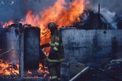 Le sapeur-pompier marche devant un petit buildig sur le feu photo libre de droits