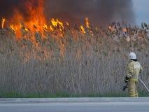 Le sapeur-pompier pense comment s'éteindre un grand feu photo libre de droits