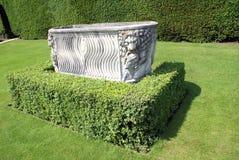 Le sarcophage romain a sculpté l'urne à un jardin formel photo stock