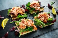 Le saumon fumé s'écaille sur le lit de salade et la pomme de terre irlandaise amincit des casse-croûte, apéritifs Image stock
