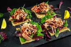 Le saumon fumé s'écaille sur le lit de salade et la pomme de terre irlandaise amincit des casse-croûte, apéritifs Photographie stock