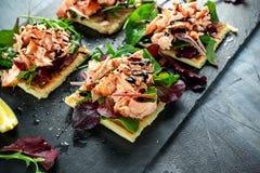 Le saumon fumé s'écaille sur le lit de salade et la pomme de terre irlandaise amincit des casse-croûte, apéritifs Images stock