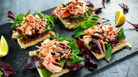 Le saumon fumé s'écaille sur le lit de salade et la pomme de terre irlandaise amincit des casse-croûte, apéritifs Photographie stock libre de droits