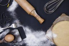 Le saupoudrage par la farine a déroulé la pâte pour le stics bakary avec la goupille en bois au-dessus du basground noir Photos stock