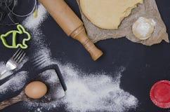 Le saupoudrage par la farine a déroulé la pâte pour le stics bakary avec la goupille en bois au-dessus du basground noir Photo stock