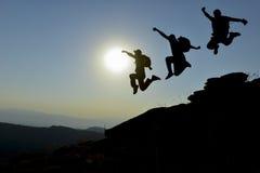 Le saut d'équipe d'aventurier et d'alpiniste apprécient images libres de droits