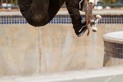 Le saut de cuvette de planche à roulettes indique la partie inférieure du corps de l'adolescent dans l'entre le ciel et la terre Image libre de droits