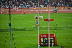 Le sauteur de pôle olympique efface le bar et gagne l'or Image stock