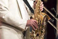 Le saxophoniste dans un costume blanc joue solo sur un saxophone Plan rapproché Photo stock