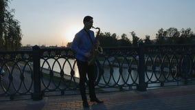 Le saxophoniste joue la trompette Remblai de ville homme avec une moustache haute barbue jouant un instrument de musique sur clips vidéos