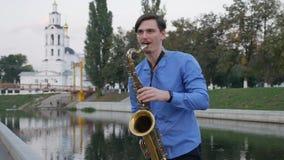 Le saxophoniste joue la trompette Remblai de ville homme avec une moustache haute barbue jouant un instrument de musique sur banque de vidéos