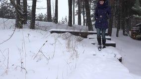 Le scale della passeggiata della donna giù coperte di neve nell'inverno parcheggiano 4K video d archivio