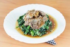 Le scalpore casalinghe hanno fritto gli spinaci, carne con il burro di noce di cocco, l'aglio, salsa di soia immagine stock