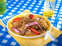 Le scalpore di Tallarin Saltado, del manzo e della tagliatella friggono, un piatto peruviano tipico Immagine Stock