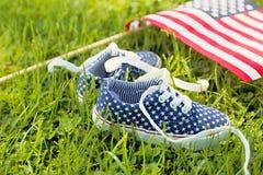 Le scarpe da tennis dei bambini americani e bandiera degli Stati Uniti d'America Immagine Stock