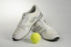 Le scarpe da tennis e una pallina da tennis degli uomini bianchi Immagini Stock