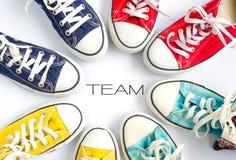 Le scarpe da tennis multicolori sul ` bianco di parola e del fondo TEAM il lavoro di gruppo di concetto del ` fotografie stock