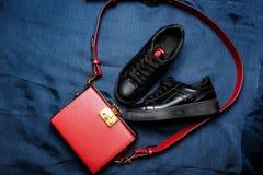 Le scarpe da tennis nere con le lingue rosse e una borsa rossa con un dorato fissano un fondo tessuto blu immagine stock libera da diritti