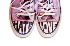 Le scarpe da tennis rosa utilizzate su misura con le parole odiano ed amano Immagine Stock