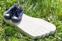 Le scarpe da tennis sono su erba e su calcestruzzo Fotografia Stock