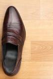 Le scarpe degli uomini classici stanno sul pavimento di legno Fotografie Stock