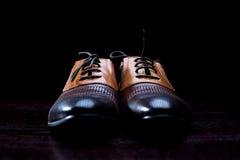 Le scarpe degli uomini di cuoio su fondo nero fotografia stock libera da diritti