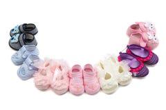 Le scarpe dei bambini risiedute in un semicerchio Immagini Stock
