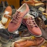 Le scarpe dei nuovi uomini sul mucchio di vecchie calzature indossate differenti fotografie stock