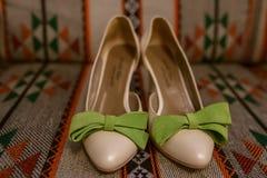 Le scarpe delicate e variopinte del ` s delle donne nelle paia, con grande pelle scamosciata verde si piega su un contesto con i  immagini stock