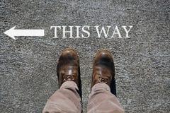 Le scarpe dell'uomo osservano da sopra, parole questo modo e una freccia che indica le direzioni con lo spazio della copia per il fotografia stock