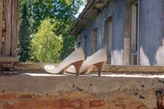Le scarpe delle alte donne bianche nella finestra Immagini Stock