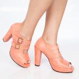 Le scarpe delle donne tallonate delle scarpe con le cinghie e fermagli dell'oro su fondo bianco immagine stock libera da diritti