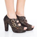 Le scarpe delle donne tallonate delle scarpe con le cinghie e fermagli dell'oro su fondo bianco fotografia stock