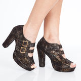 Le scarpe delle donne tallonate delle scarpe con le cinghie e fermagli dell'oro su fondo bianco immagini stock