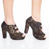 Le scarpe delle donne tallonate delle scarpe con le cinghie e fermagli dell'oro su fondo bianco fotografia stock libera da diritti