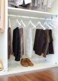 Le scarpe di cuoio di Brown e la fila dei pantaloni neri appende in guardaroba Immagine Stock Libera da Diritti