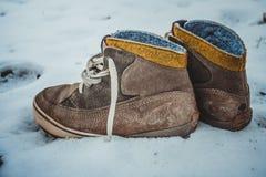 Le scarpe di cuoio sono state lasciate sole nella neve immagine stock