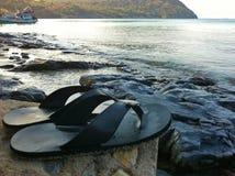 Le scarpe di Flip-flop hanno messo sopra la parte anteriore di pietra la spiaggia immagine stock