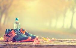 Le scarpe e l'acqua blu di sport hanno messo su un bordo di legno immagini stock
