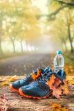 Le scarpe e l'acqua blu di sport hanno messo su un bordo di legno fotografia stock libera da diritti
