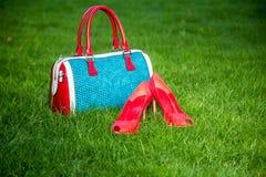 Le scarpe e la borsa delle donne mettono sull'erba, le scarpe delle donne Fotografie Stock Libere da Diritti
