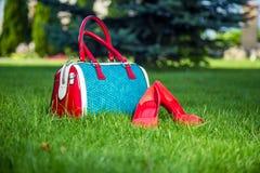 Le scarpe e la borsa mettono sull'erba, le scarpe delle donne Fotografia Stock Libera da Diritti