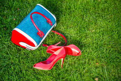 Le scarpe e la borsa mettono sull'erba, le scarpe delle donne Immagine Stock