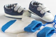 Le scarpe ed i guanti dei bambini su un bianco Fotografia Stock