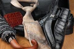 Le scarpe, il legame, l'ombrello, il portafoglio e la borsa degli uomini classici sul di legno Fotografie Stock